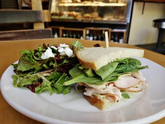 "Pavo Diablo: hickory-smoked turkey, sliced avocado, spinach, havarti, roasted poblano peppers, spicy chipotle aioli, and cilantro on sourdough bread (a ""soft and comforting"" half sandwich that wasn't really spicy), served with a nice house salad"