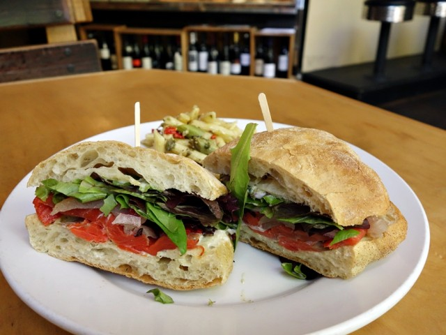 The Seattle Cure: cured albacore tuna bresaola, salmon lox, lemon-caper aioli, shaved red onions, sweet peppers, and field greens on a toasted ciabatta roll (the lox flavor prevails), served with pasta salad with asparagus