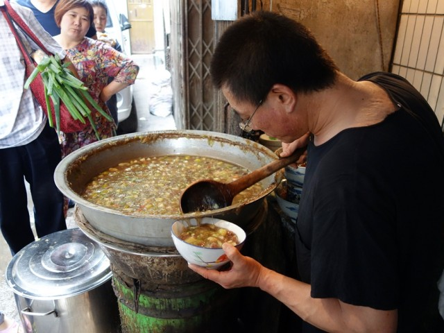 "People line up (some with large ""canteens"" for to-go orders) to get ma la (numbing spicy) soup"