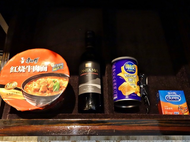 Inside the Hilton guest room, all the supplies one needs: noodles, wine, potato chips, and condoms