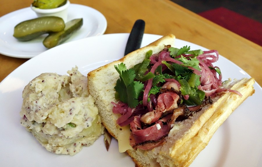 Best sandwich of the visit was The Rebel: hot pastrami with white cheddar, jalapeno-lime aioli, picked red onions, jalapenos, and cilantro on a 10″ Italian roll (half sandwich shown), served here with potato salad and pickles