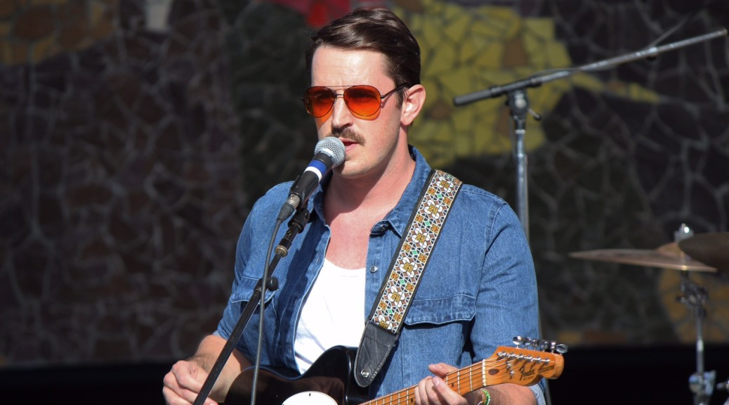 Local singer/songwriter Kris Orlowski moments before he passed matching mustaches into the crowd.